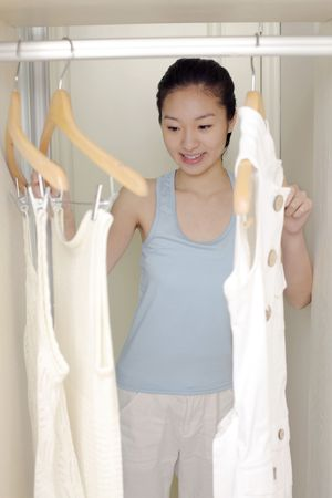 choosing clothes: Young woman choosing clothes in the wardrobe