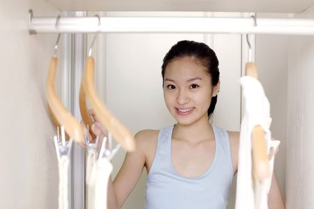 Young woman choosing clothes in the wardrobe