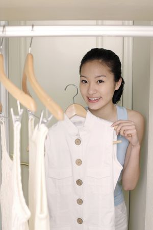 Young woman choosing clothes in the wardrobe photo