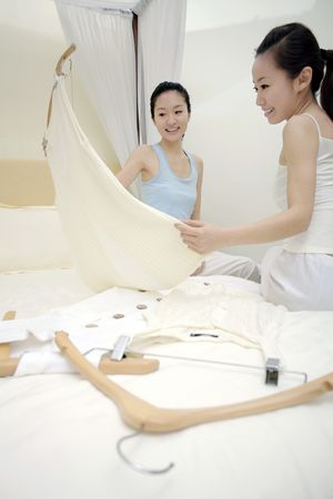 choosing clothes: Young women choosing clothes in bed Stock Photo