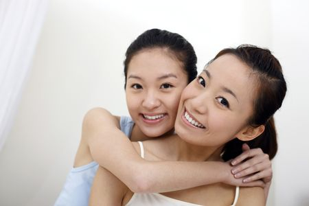 Young woman hugging her friend from the back Stock Photo