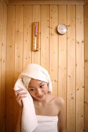 Young woman in sauna, wiping sweat photo