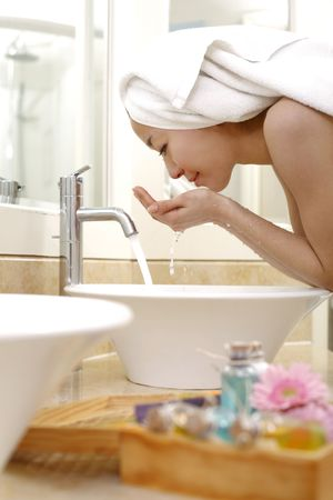 Young woman washing face at bathroom sink photo