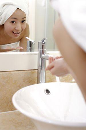 lavabo salle de bain: Jeune femme face au r�cepteur de salle de bains de lavage. Banque d'images