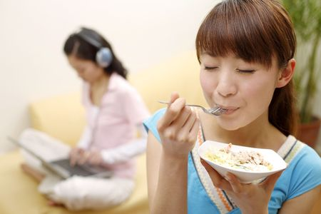 Young woman enjoying her food, another woman listening to music and using laptop photo