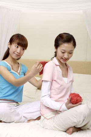 two people only: Young woman measuring her friends back while knitting Stock Photo