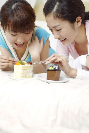 Young women enjoying cake together photo