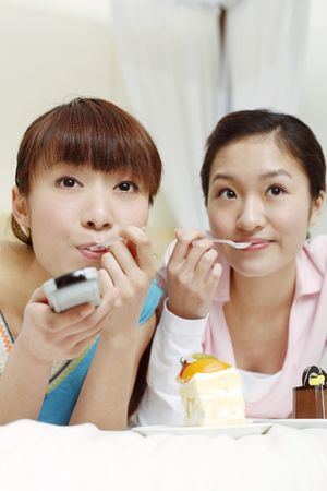Young women eating cakes while watching television photo