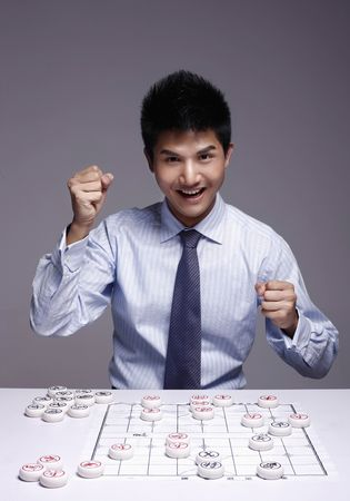 Businessman cheering after winning the chinese chess game photo