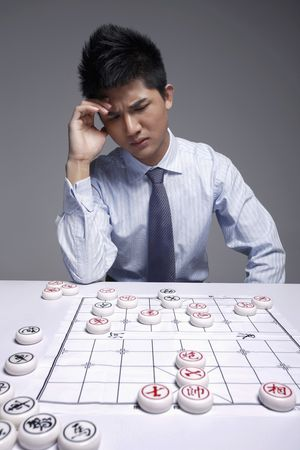Businessman thinking with hand on head while playing chinese chess photo