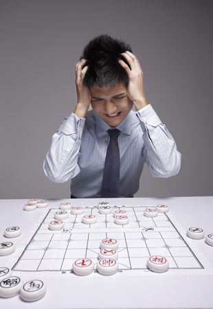 Businessman frowning with hands on head while playing chinese chess photo
