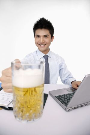 beer and necktie: Businessman holding a glass of beer while using laptop