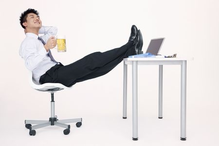 Businessman enjoying a glass of beer with his legs on the table photo
