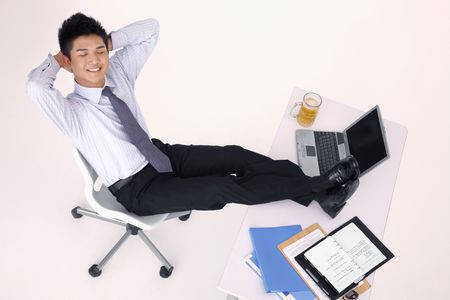 Businessman sitting with his arms crossed behind and his legs on the table photo
