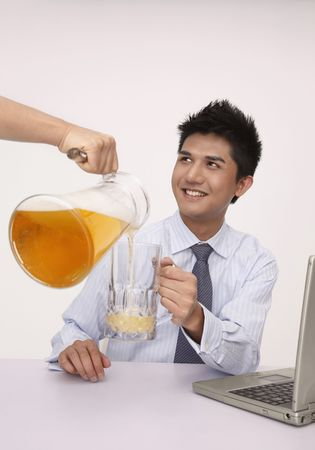 necktie beer: Hand pouring a jug of beer into businessmans glass Stock Photo