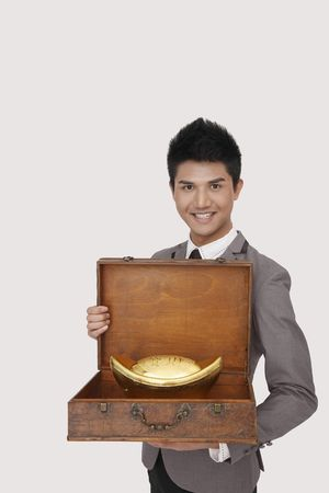 Businessman showing gold ingot in wooden briefcase photo