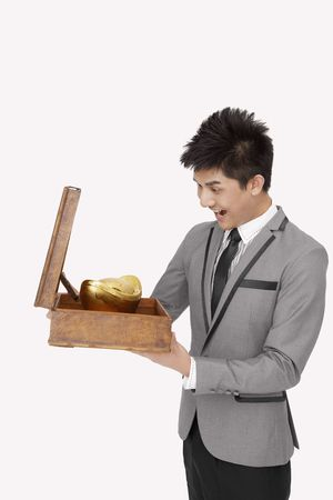 Businessman looking at gold ingot with his mouth wide opened photo