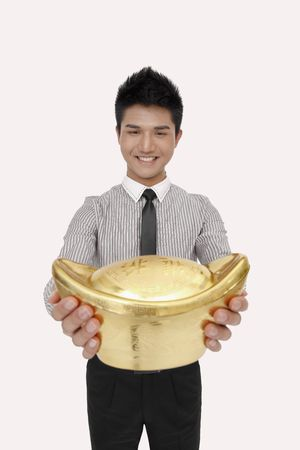 Businessman smiling while holding a big gold ingot photo
