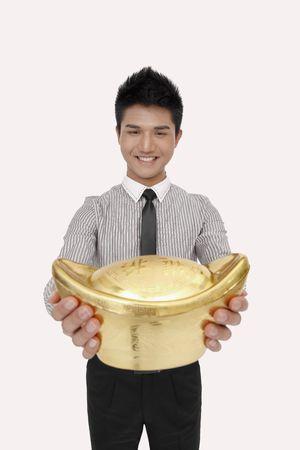 Businessman smiling while holding a big gold ingot photo