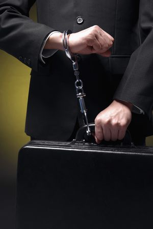 Businessman handcuffed to briefcase photo