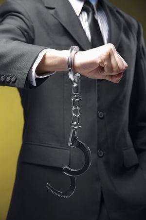 Businessman handcuffed on one hand photo