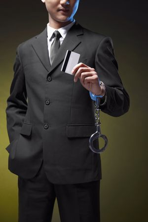 Businessman handcuffed on one hand and holding credit card Stock Photo