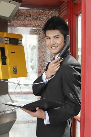 Businessman holding organizer and pen while talking on a pay phone photo