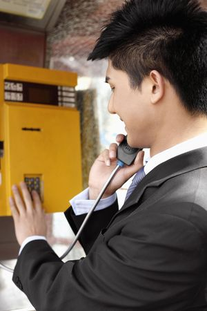 Businessman using a pay phone photo