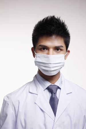 Businessman in surgical mask and lab coat photo
