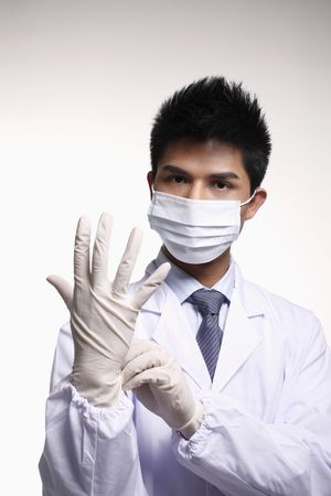 Businessman in surgical mask and lab coat putting on rubber glove photo