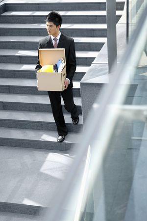 belongings: Businessman carrying box of belongings walking down the stairs Stock Photo