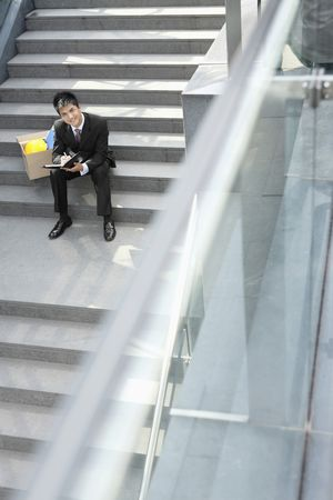 Businessman sitting on staircase writing on organizer photo