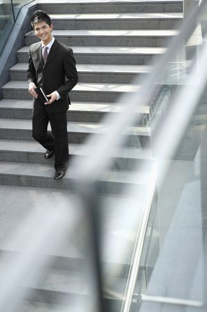 Businessman holding organizer and walking down the stairs Stock Photo - 4810501