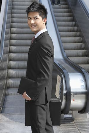 Businessman holding organizer and carrying briefcase Stock Photo - 4810613
