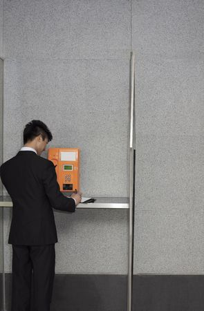 Businessman writing on organizer while talking on pay phone photo