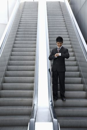 Businessman checking time on watch while standing on escalator photo