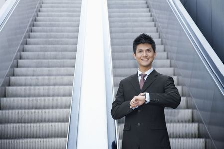 Businessman checking time on watch while standing on escalator Stock Photo - 4810744