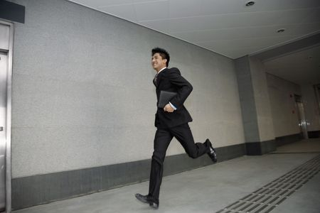 Businessman running while holding organizer