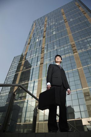 Businessman with briefcase standing in front of a building photo