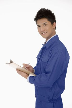 Businessman in protective workwear writing report Stock Photo