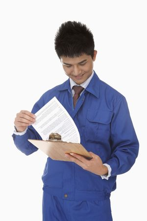 Businessman in protective workwear reading report photo