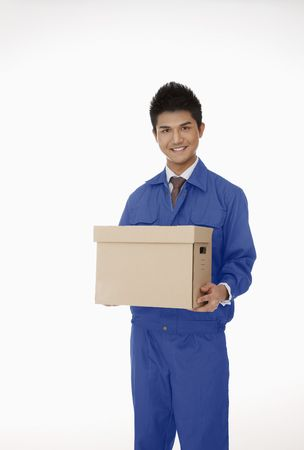 Businessman in protective workwear carrying a box photo
