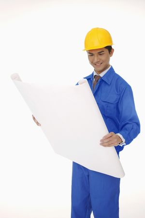 Businessman in protective workwear looking at blueprint