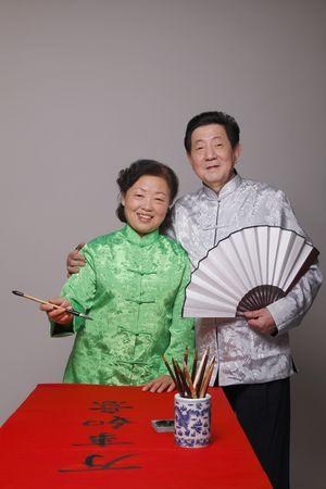 Senior woman holding calligraphy brush, senior man holding folding fan beside her Stock Photo - 4810715