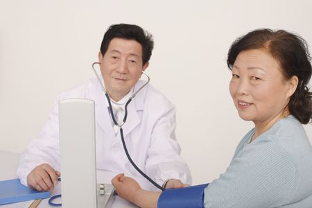 Doctor examining patients blood pressure