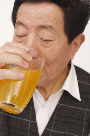 Senior man drinking a glass of remedy photo