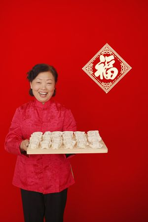 Senior woman holding up cutting board with chinese dumplings