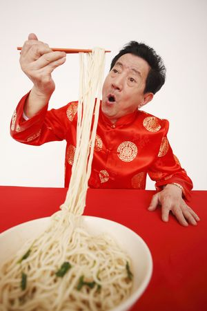 Senior man enjoying his bowl of noodles Stock Photo