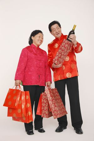 Senior woman holding shopping bags while senior man is showing her a bottle of wine Stock Photo