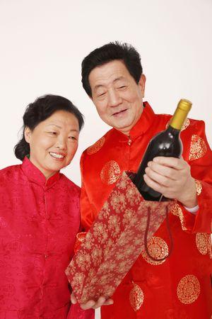 Senior man is showing senior woman a bottle of wine photo